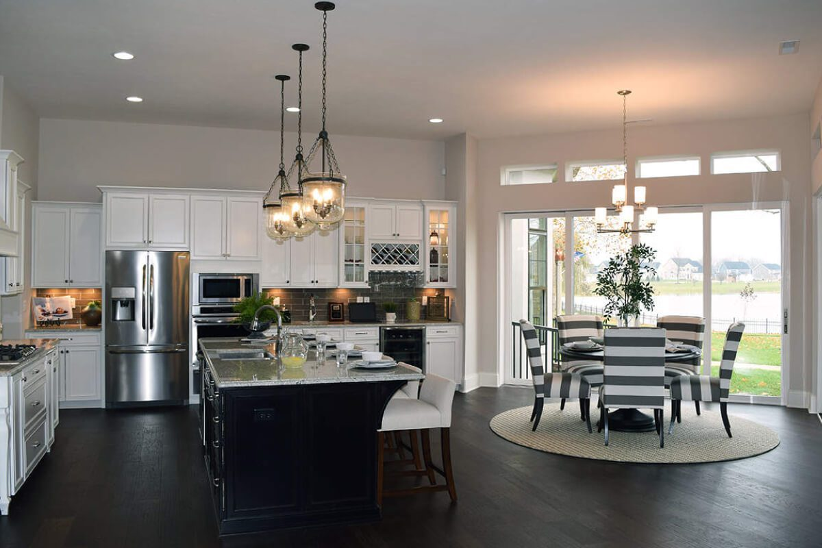 spacious white kitchen with fridge and dining room table in one of Waterfront of West Clay's custom homes