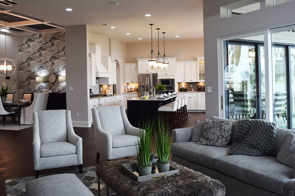 Grey couch and decorative chairs in the living room of one of Waterfront of West Clay's custom home