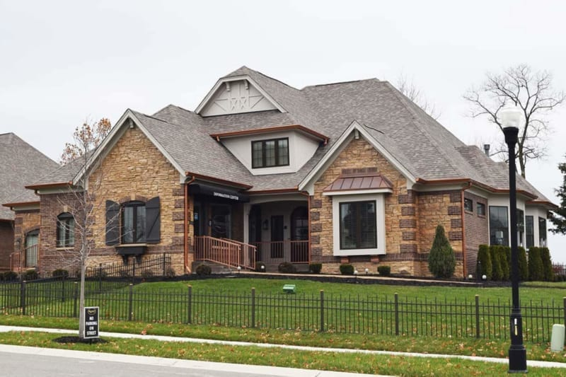 Custom home with tan stone, red brick, and black shutters that doubles as Waterfront of West Clay's information center