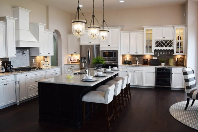 spacious white kitchen with fridge, kitchen island, breakfast bar, and gas stove in one of Waterfront of West Clay's custom homes