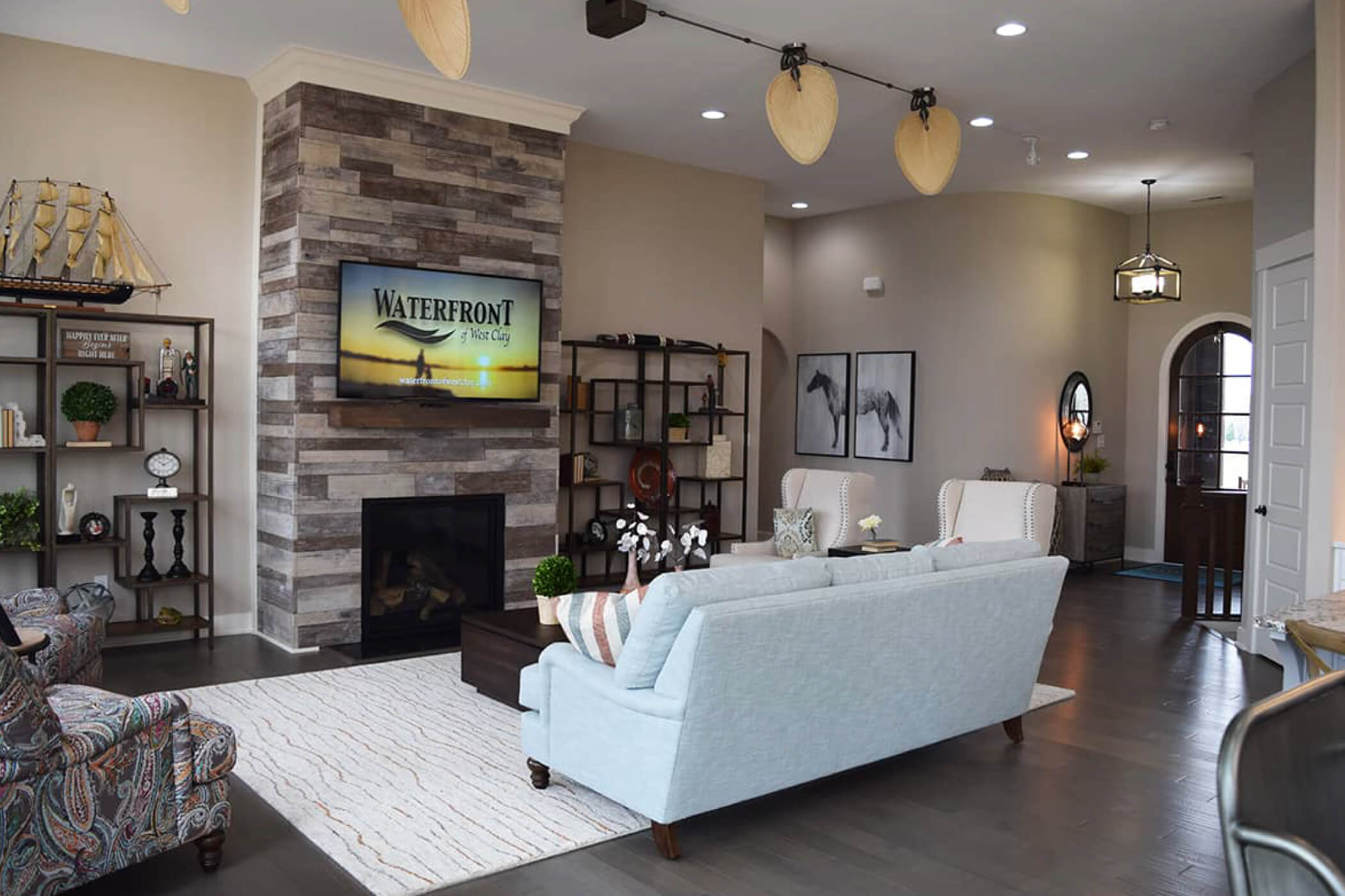 Blue couch with tan decorative chairs facing a television showing the Waterfront of West Clay custom homes slideshow