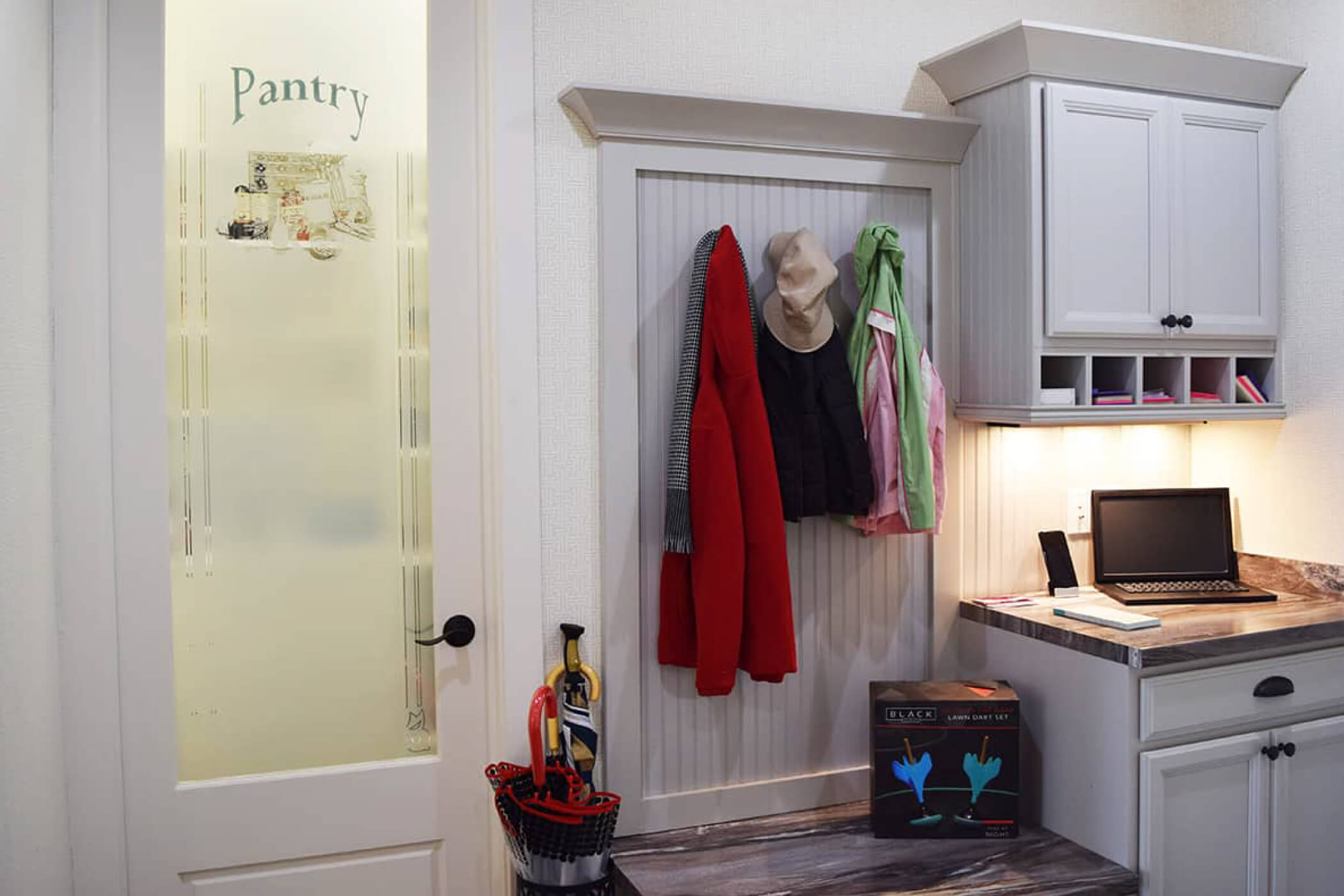 Mud room with red jacket hanging above the landing station in a custom home located in Carmel
