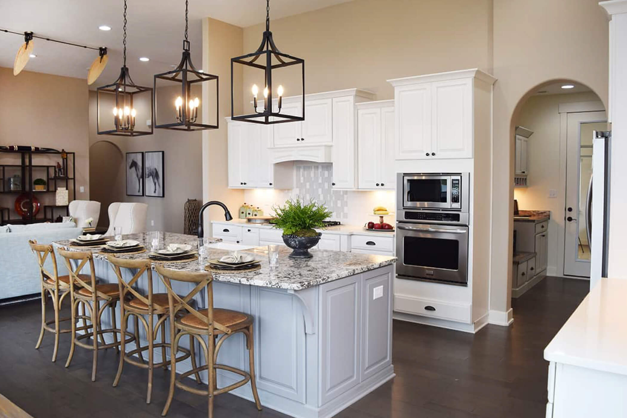 White kitchen cabines, granite island, breakfast bar, and gas stove in the kitchen of one of Waterfront of West Clay's custom homes