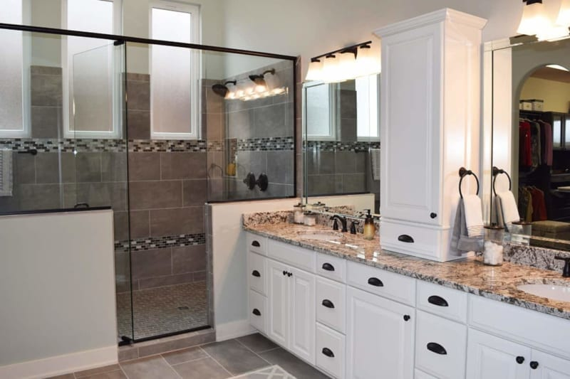 Double sink vanity with white cabinets in the master bathroom of a Carmel located custom home
