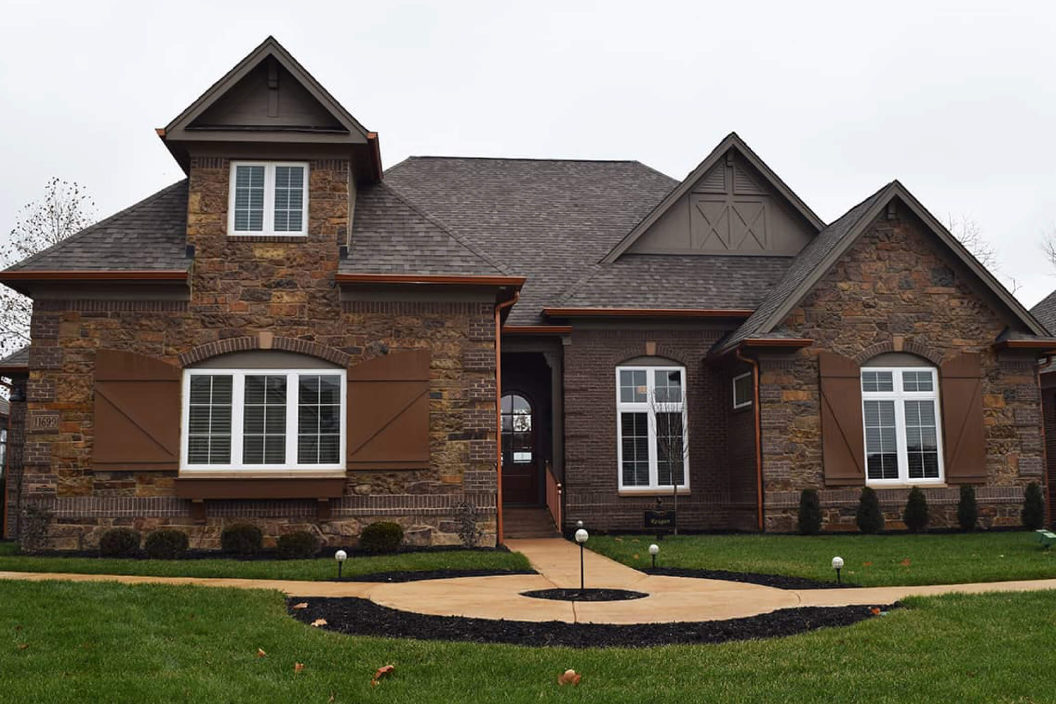 Brown brick, one-story custom home sitting on a grassy lot in Waterfront of West Clay
