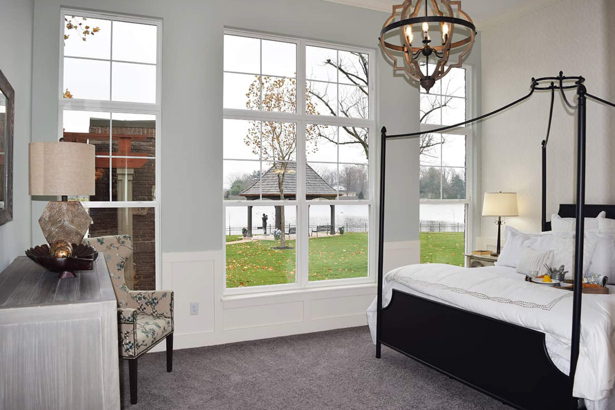 King bed with white sheets and throw pillows overlooking the lake in Waterfront of West Clay