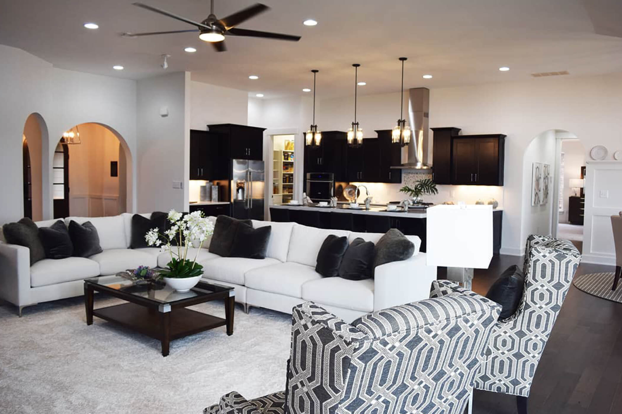 White sectional couch with black pillows sitting in the living room of one of Waterfront of West Clay's Carmel, IN custom homes