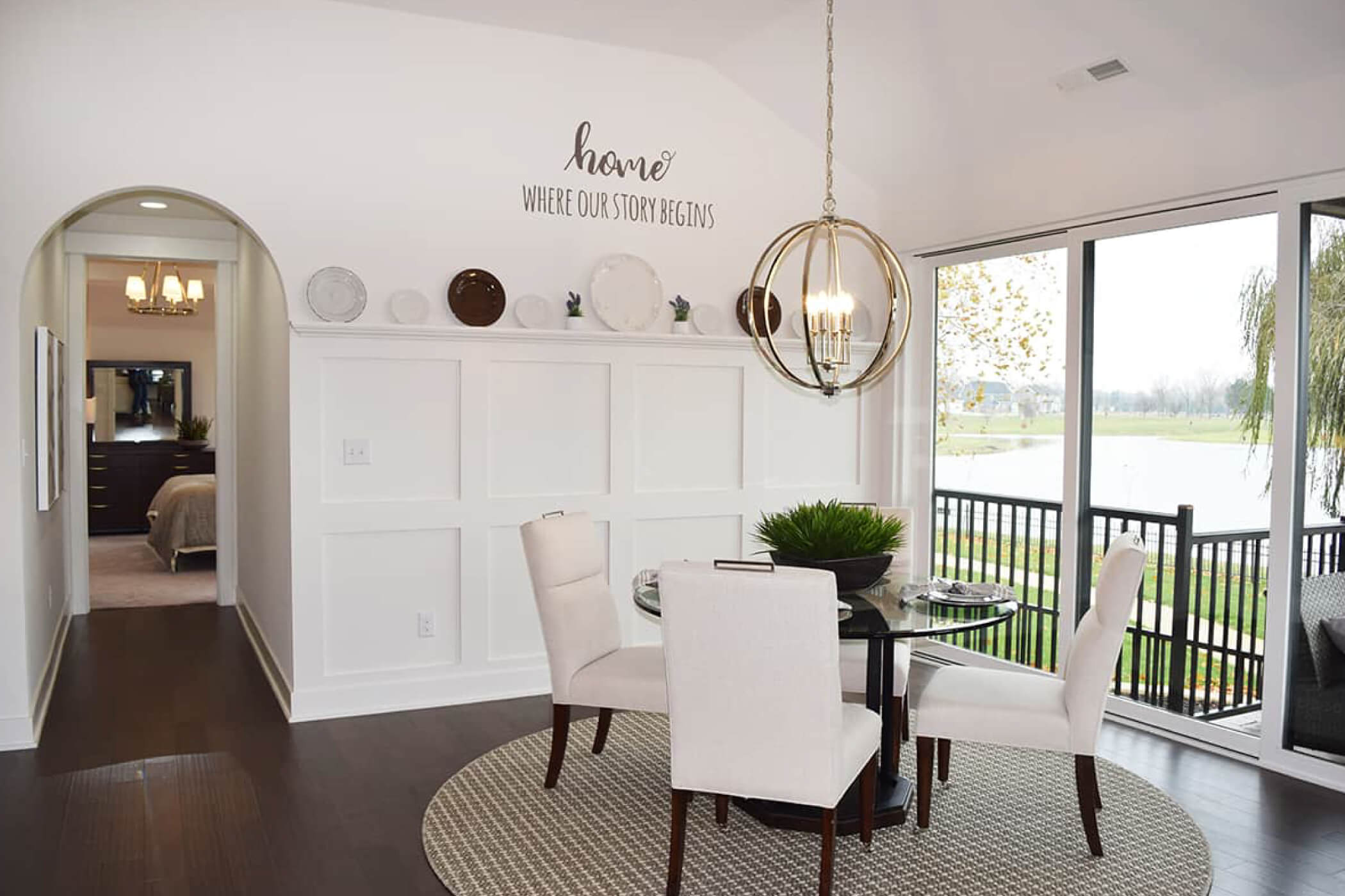 Circle dining room table with four white chairs in the dining room of one of Waterfront of West Clay's custom homes