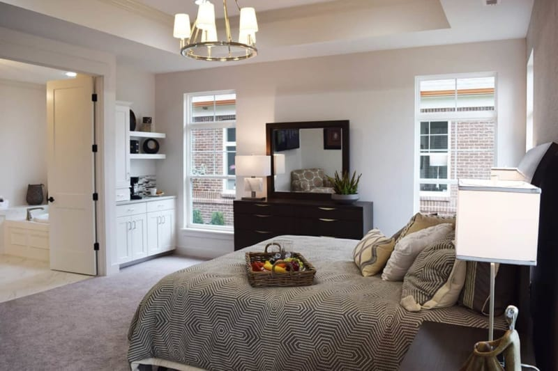 Queen bed against white wall in master bedroom of one of Waterfront of West Clay's custom built homes