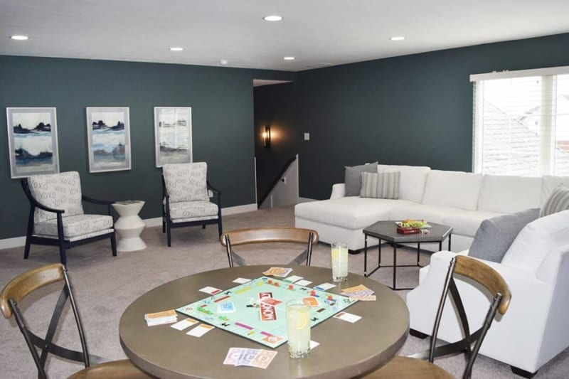 White sectional couch, game table with Monopoly game in loft space of a one of Waterfront of West Clay's custom Carmel, Indiana homes