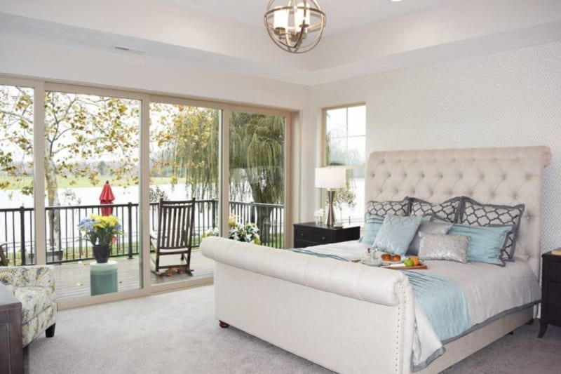 Queen bed with plush white headboard and grey throw pillows in the bedroom of a custom home in Carmel, IN