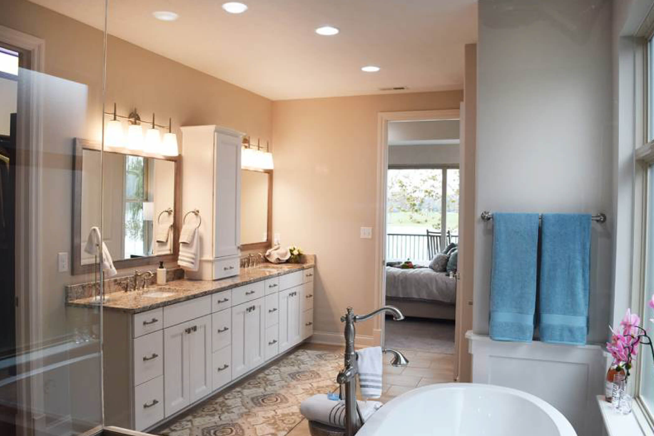 Master bathroom with double vanity, tile flooring, and bath tub in one of Waterfront of West Clays Carmel custom homes