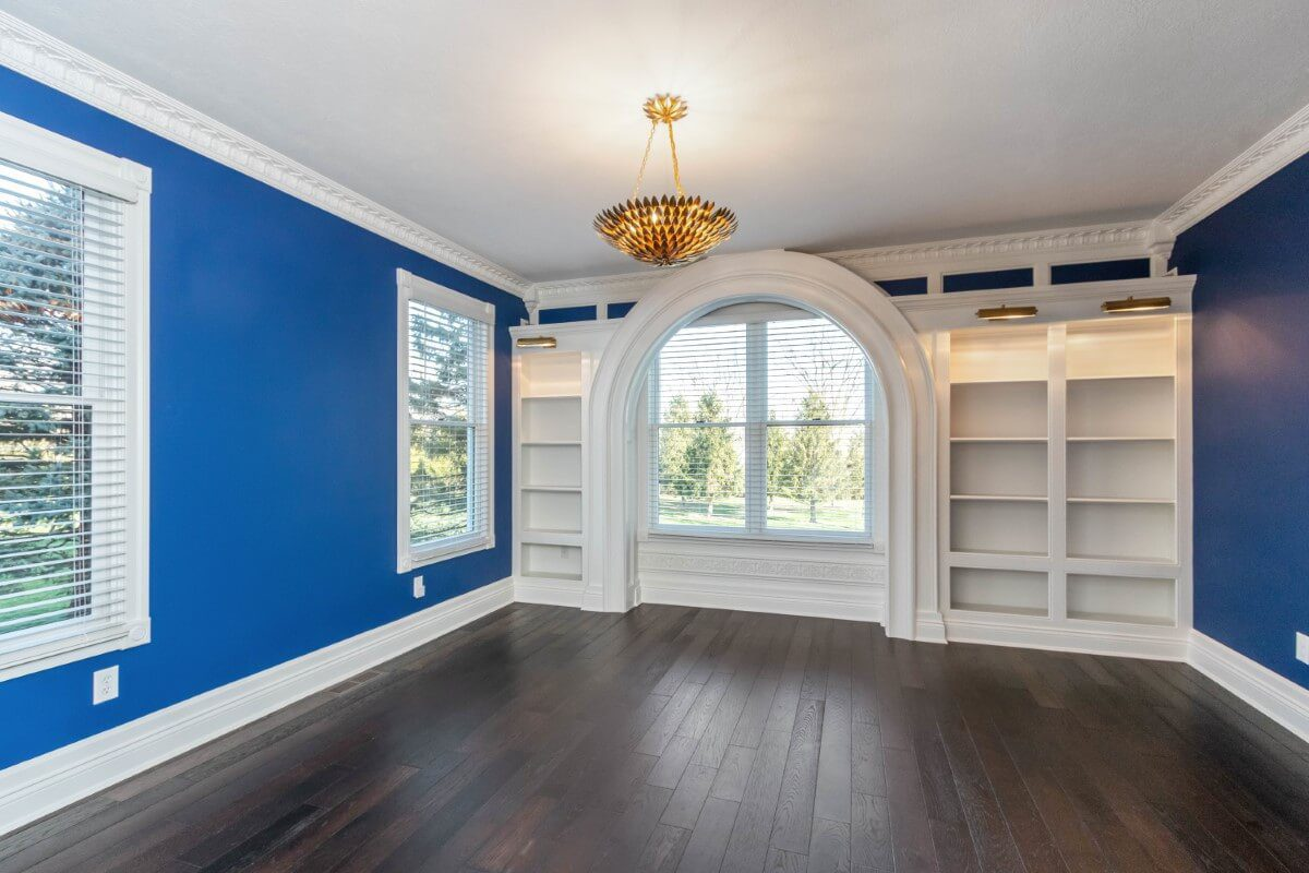 in home office with bright blue walls and build in storage